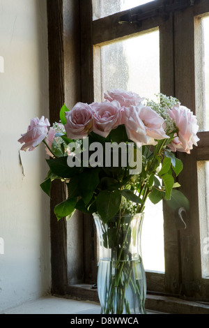 Bouquet of roses on the old windowsill with wooden window frames. - Stock Image