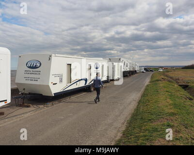 Leysdown, Kent, UK. 26th March, 2018. An ITV production crew prepares to film Dark Heart in Leysdown, a new ITV crime series. It stars Tom Riley (believed to be pictured walking by in this photo). Credit: James Bell/Alamy Live News - Stock Image