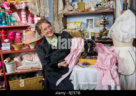 Lady volunteer in Victorian costume shows her skills at the sewing machine, Blists Hill Victorian Town, Shropshire, UK - Stock Image