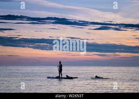 Aberystwyth Wales UK, Tuesday 09 July 2019  UK Weather: People silhouetted against the colours of the sunset as they paddleboard on the flat calm sea off the beach in Aberystwyth at the end of a warm summers day  in west Wales.   photo credit: Keith Morris//Alamy Live News - Stock Image