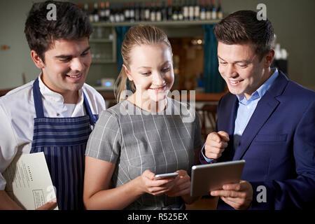 Restaurant Team Discussing Menu Looking At Digital Tablet - Stock Image