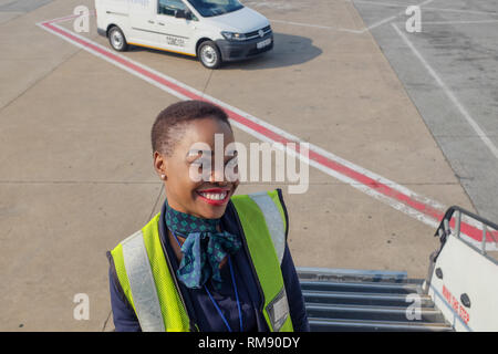 An airline employee stands on the steps leading up to a British Airways flight from Johannesburg to Cape Town after passengers have boarded. - Stock Image