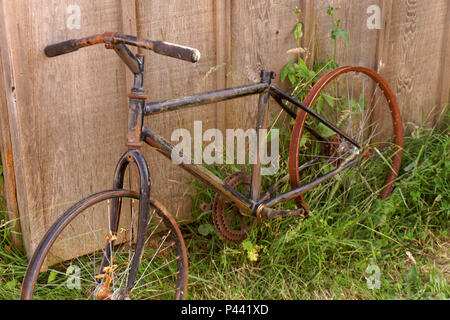 Rusty bicycle leaning against a wooden fence - Stock Image