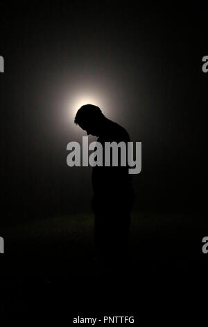Silhouette in the Dark, Head Leaning Forward with Light behind - Stock Image
