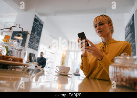 Blond businesswoman using smartphone in a coffee shop, reading text messages - Stock Image