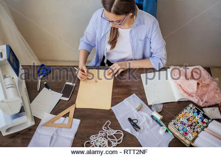 Young caucasian female dress designer in casual wear is drawing sketches of new men and women s apparel , summer collection - Stock Image