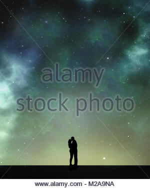 Couple kissing silhouetted against starlit sky - Stock Image