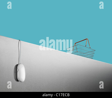 Conceptual photograph illustrating internet shopping with a computer mouse and shopping basket - Stock Image