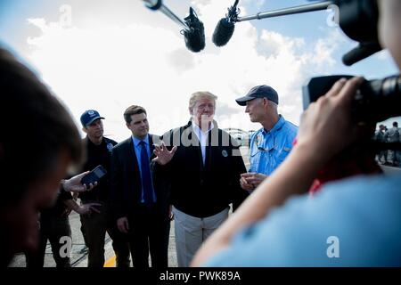 Panama City, Florida, USA. 15th Oct 2018. U.S President Donald Trump, center, alongside Florida Governor Rick Scott, right, speak with the media after viewing damage from Hurricane Michael at Eglin Air Force Base October 15, 2018 in Valparaiso, Florida. Credit: Planetpix/Alamy Live News - Stock Image