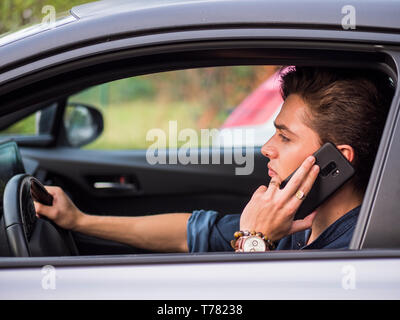 Attractive young man sitting in his car talking on cell phone, while driving - Stock Image