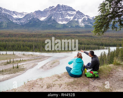Lunch With a Mountain View: A man and a woman share lunch at a lookout point on the Ice Fields Parkway in Jasper National Park. He points toward the mountain range. The Athabaska river flows below. - Stock Image