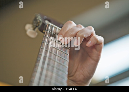 close-up of young woman playing guitar - Stock Image