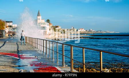 Estoril, Portugal - Dec 8, 2018: Spray from waves splashing on boardwalk leading to Tamariz beach in the Atlantic resort town of Estoril near Lisbon,  - Stock Image