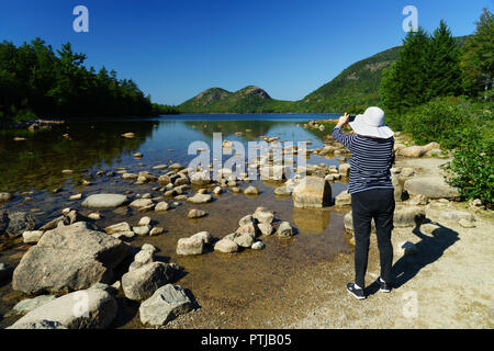 Woman taking a picture of Jordan Pond with her mobile phone.Acadia National Park, Maine, USA. - Stock Image
