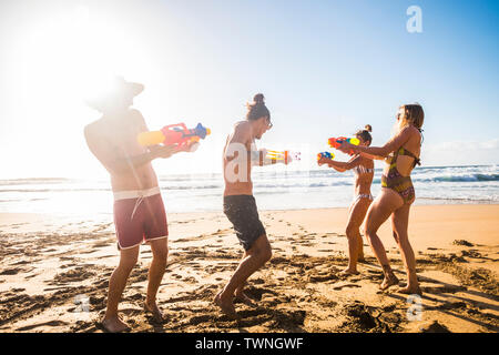 Group of friends play at the beach with water guns during happy summer holiday vacation - concept of young people enjoying friendship and outdoor play - Stock Image