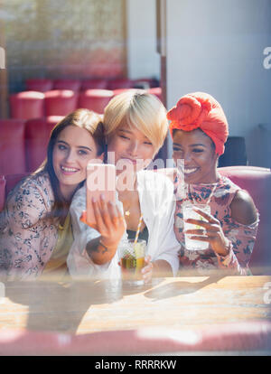 Young women friends drinking cocktails and posing for selfie in sunny restaurant - Stock Image