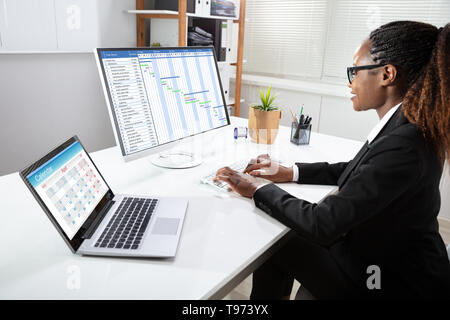Young African Businesswoman Analyzing Gantt Chart On Computer At Workplace - Stock Image