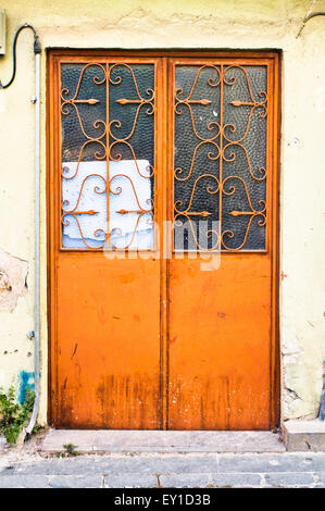 A double door painted orange in a stone wall - Stock Image