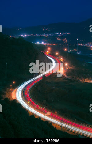 Car light trails in highway at night - Stock Image
