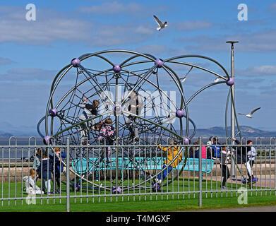 Children playing on a climbing frame. The Promenade,  Morecambe, Lancashire, England, United Kingdom, Europe. - Stock Image