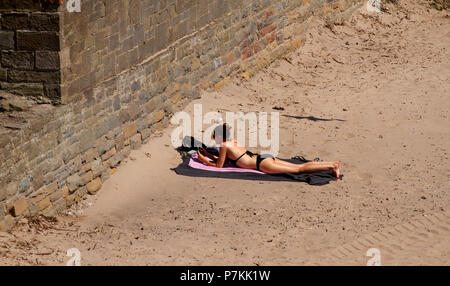 Dundee, Tayside, Scotland, UK. 7th July, 2018. UK weather: The heatwave continues with temperatures reaching 24º Celsius. A woman sunbathing at Broughty Ferry beach in Dundee , UK. Credits: Dundee Photographics / Alamy Live News - Stock Image