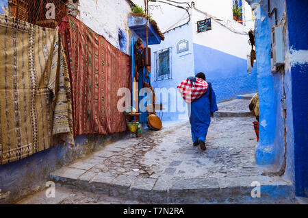 Chefchaouen, Morocco : A woman carries a sack past traditional carpets in the blue-washed alleyways of the medina old town. - Stock Image