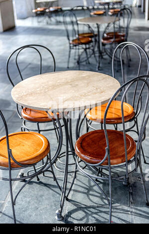 Empty sidewalk café with table and wrought iron chairs - Stock Image