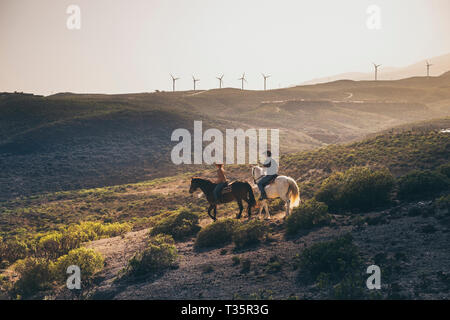 Beautiful landscape on mountain with windmills in background and couple of people riding horse for excursion on alternative cowboy farm lifestyle - su - Stock Image