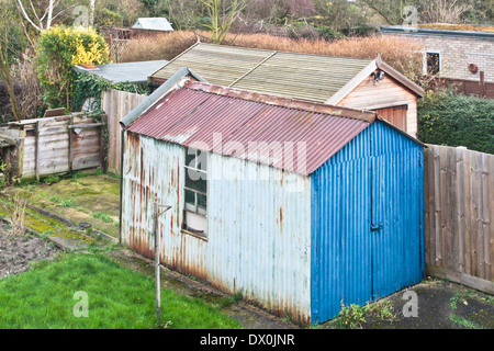A rusty metal garden shed in an english home - Stock Image