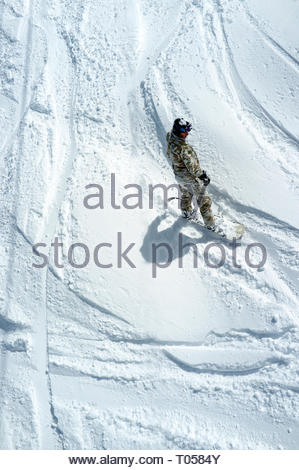 A snowboarder seen from above, off piste, at the ski resort in Sainte-Foy-Tarentaise, Auvergne-Rhône-Alpes region in south-eastern France. - Stock Image