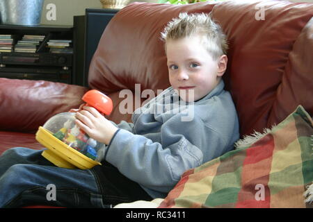 Young boy with humming top on sofa indoors, look at camera - Stock Image