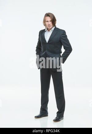 The handsome men in black suits differently pose on a white background, hands in trouser pockets - Stock Image
