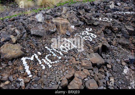 White pebble graffiti on black lava rock. Kona, Big Island, Hawaii - Stock Image