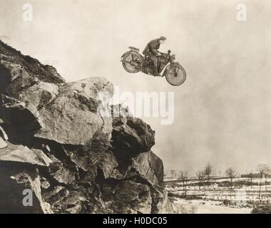 Stuntman on motorbike flying over cliff - Stock Image