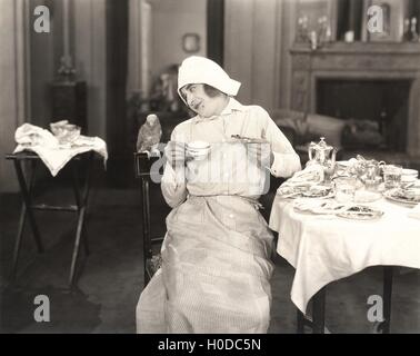 Maid joined by a fine feathered friend for breakfast - Stock Image