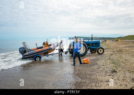 Three men using a tractor to recover their Rigid Inflatabe boat after an angling expdition off the North Yorkshire Coast - Stock Image