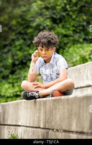 Solemn little boy wearing yellow sunglasses seated on a concrete step outdoors lowering the glasses to peer over at the camera - Stock Image