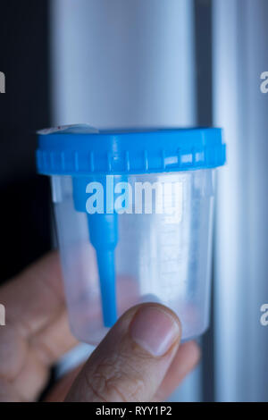 Medical urine test cup to hold patient dope testing anti drugs, sample. - Stock Image