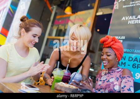 Young women friends enjoying smoothies at sidewalk cafe - Stock Image