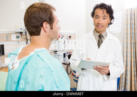 Doctor Holding Digital Tablet By Patient In Hospital - Stock Image