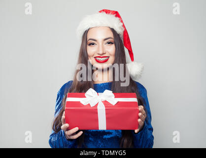 Happy woman in braces and Christmas gift on white - Stock Image