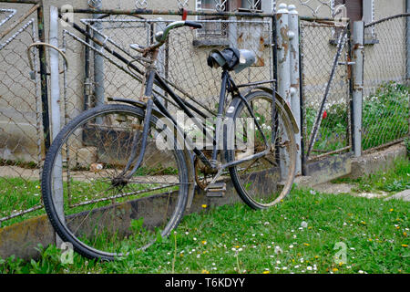 old fashioned bicycle propped against a fence in a rural village zala county hungary - Stock Image