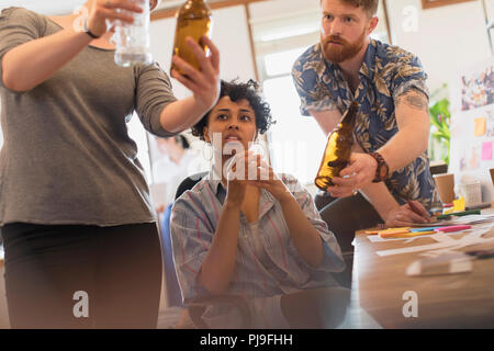 Creative designers examining bottles in office - Stock Image