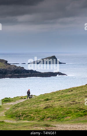 A man walking alone along the coastal path on Pentire Point East in Newquay in Cornwall - Stock Image