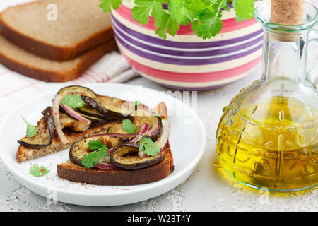 Gourmet rye bread sandwich with fried or baked eggplant, red onion, cilantro and spices. Mediterranean appetizer.  Selective focus - Stock Image