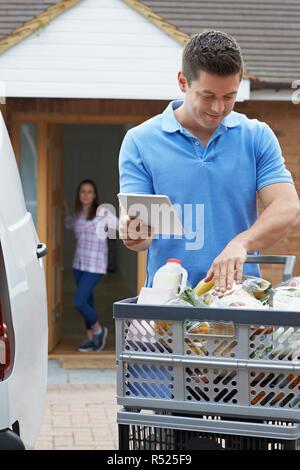 Driver Delivering Online Grocery Order To House Using Digital Tablet - Stock Image