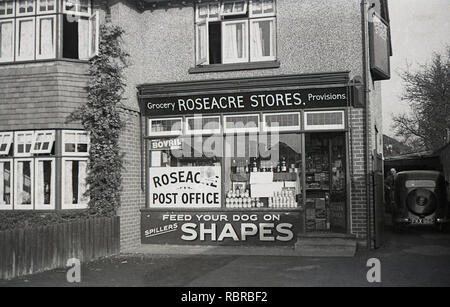 1950s, historical, car of the era parked beside Roseacre Stores and Post Office, Kent, England, UK. Corner shops such as these which sold groceries, household items and also had a post office, were common place in England at this time and although having large supermarket competitors, many have survived based on personal service and convenience and increasingy are becoming community owned and run. - Stock Image