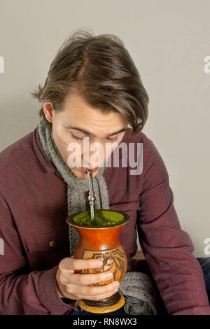 Young man driking the Brazilian traditional mate-based drink (chimarrao) from a gourd container (cuia) against white background, front view - Stock Image