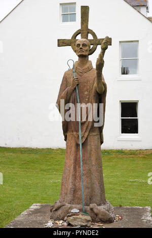 Statue of St Aidan first bishop of Lindisfarne monastery with white Manor House Hotel on Holy Island at the Priory ruins England UK - Stock Image