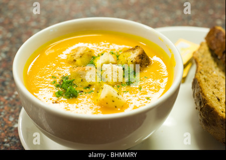 image of bowl of pumpkin soup with croutons and brown bread - Stock Image